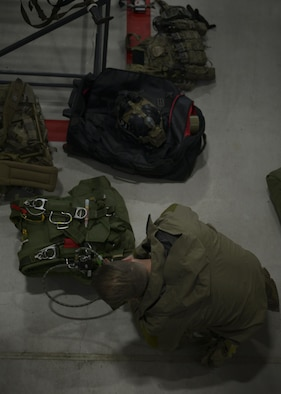 An Air Commando from the 321st Special Tactics Squadron affixes an oxygen tank to a parachute pack in preparation for a high altitude, low opening parachute jump Dec. 14, 2016, on RAF Mildenhall, England. A HALO jump is a Military Free Fall and, without oxygen, can render the jumper unconscious. (U.S. Air Force photo by Staff Sgt. Victoria H. Taylor)