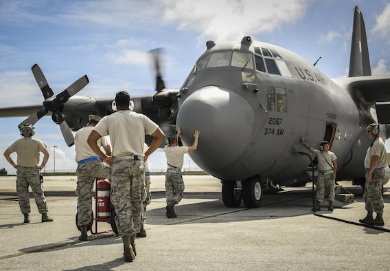 C-130H Hercules maintainers, assigned to the 374th Maintenance Group, prepare an aircraft for takeoff during Operation Christmas Drop 2016 at Andersen Air Force Base, Guam, Dec. 7, 2016. The maintainers of OCD adapted to a high operational tempo and made sure aircraft were safe and ready to fly daily. (U.S. Air Force photo/Senior Airman Elizabeth Baker)