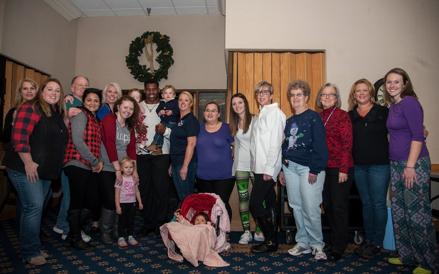 Former Heisman Trophy winner Herschel Walker takes a moment to pose with members of the Kirtland Spouses' Club during his visit to Kirtland Dec. 12-13.  Walker spoke at multiple venues on base, detailing his struggles with mental illness and encouraging those with issues to seek help.