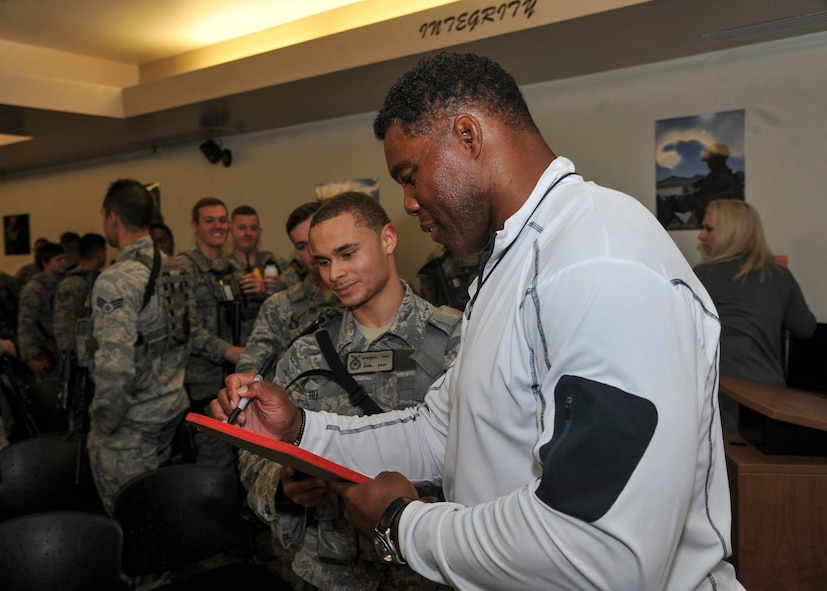 Former Heisman Trophy winner Herschel Walker signs autographs following his visit with Airmen in the 377th Weapons System Security Squadron during his visit to Kirtland Dec. 12-13. Walker spoke at multiple venues on base, detailing his struggles with mental illness and encouraging those with issues to seek help.