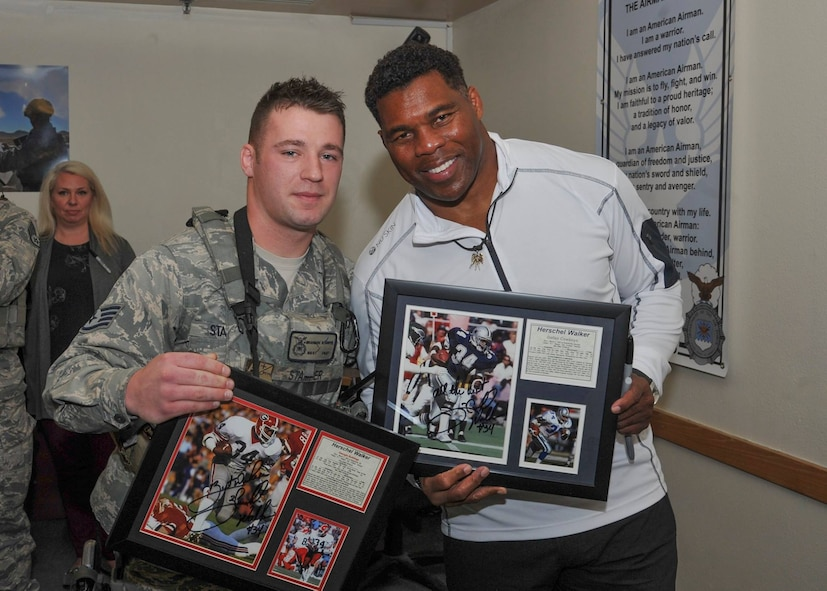 Former pro football player Herschel Walker poses with plaques he signed for Staff Sgt. Brandon Stamper of the 377th Weapons System Security Squadron during his visit to the base Dec. 12-13. Walker came to the base to tell Airmen about his suffering with a mental illness. He said there is no shame in asking for help.