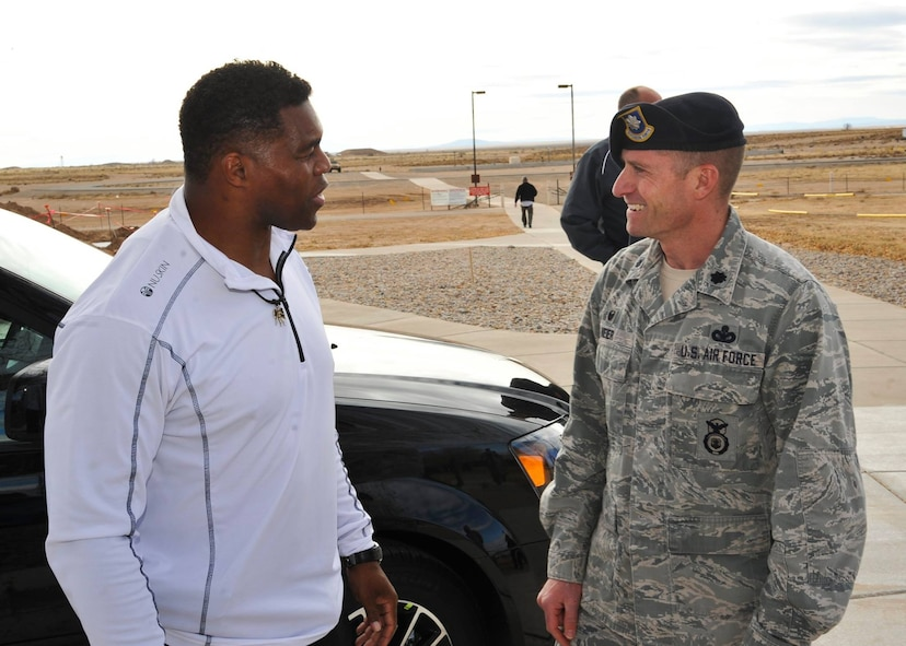 Former Heisman Trophy winner Herschel Walker chats with Lt. Col. James Meier, 377th Weapons System Security Squadron commander, during his visit to Kirtland Dec. 12-13.  Walker spoke at multiple venues, detailing his struggles with mental illness and encouraging those with issues to seek help.