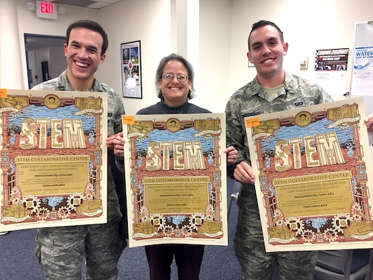 Air Force Research Laboratory mentors, from left, Capt. Timothy Wolfe, Imelda Atencio and 2nd Lt. Evan Threlkeld hold posters announcing the University of New Mexico STEM Collaborative Center during a visit to that center. The mentoring program matches UNM undergraduate students with AFRL scientists and engineers, military or civilian, to provide personal and professional mentorship.