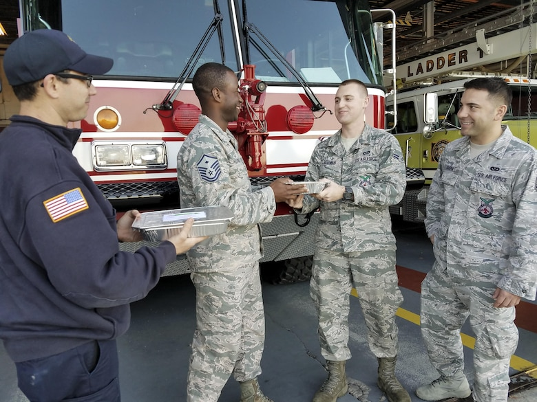 Master Sgt. Travis Heath, 628th Civil Engineer Squadron first sergeant, left, hands cookies to members of the fire department Dec. 7, 2016. The cookies were made by the Team Charleston Spouses Club for the annual holiday program: Operation Cookie Drop.