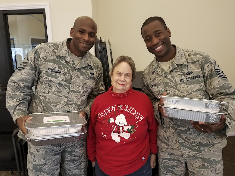 Master Sgt. Derrick Sherrod, 437th Maintenance Squadron first sergeant, left, and Master Sgt. Travis Heath, 628th Civil Engineer Squadron first sergeant, right, stand with June Griggs, Team Charleston Spouses Club member, when receiving cookies at the Hunt Housing Office Dec. 7, 2016. The cookies were made for the annual holiday program: Operation Cookie Drop where spouses baked cookies for Joint Base Charleston members working the mid, swing and night shifts.