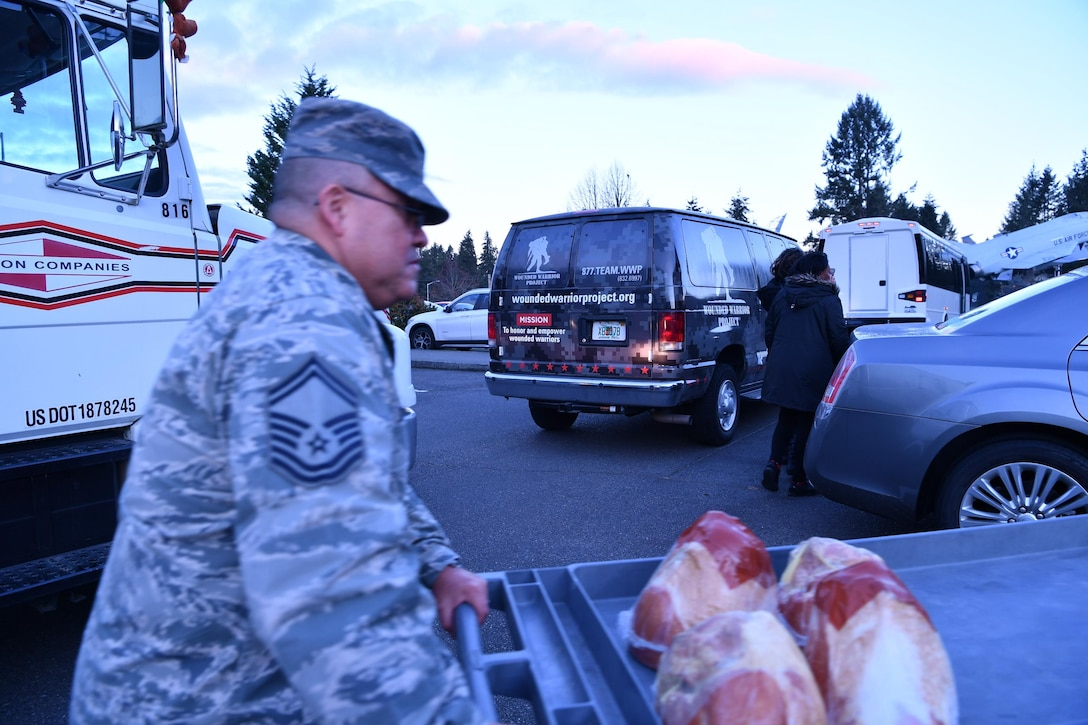 Senior Master Sgt. Carlos Gonzales, 225th Support Squadron, transports donated holiday hams during Operation Ham Grenade, sponsored by the Association of the United States Army, Air Force Association, and Pierce Military and Business Alliance, into the Western Air Defense Sector building Dec. 16.  (U.S. Air National Guard photo by Kimberly D. Burke)