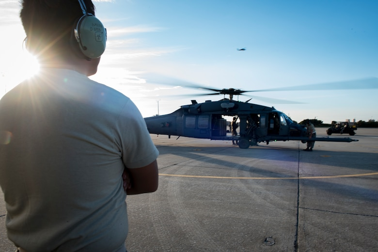 Senior Airman Aaron Mier, 41st Helicopter Maintenance Unit crew chief, watches as an HH-60G Pave Hawk prepares to launch, Dec. 12, 2016, at Patrick Air Force Base, Fla. Airmen performed hot refueling and crew changes, meaning the aircraft never shut off during the procedures. (U.S. Air Force photo by Airman 1st Class Daniel Snider)
