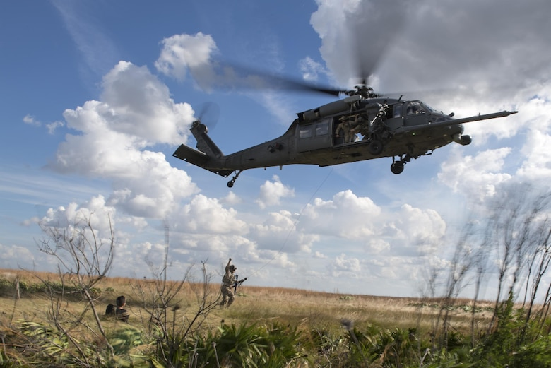 A paraescueman from the 38th Rescue Squadron communicates with aircrew from the 41st Rescue Squadron before hoisting the simulated stranded survivor into a HH-60G Pave Hawk, Dec. 12, 2016, at Avon Park Air Force Range, Fla. Airmen would randomly place themselves in the range and pretend to be a stranded survivor, providing aircrews the opportunity to practice their combat, search and rescue mission. (U.S. Air Force photo by Airman 1st Class Daniel Snider)