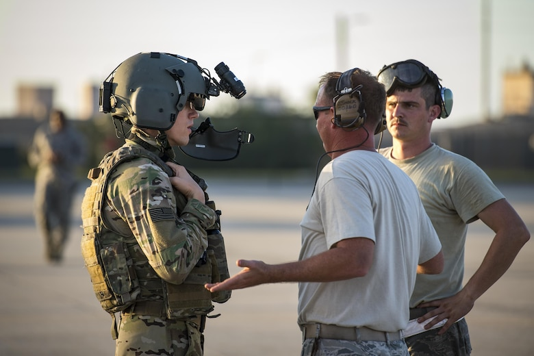 """An aircrew member from the 41st Rescue Squadron discusses the maintenance status of an HH-60G Pave Hawk with airmen from the 41st Helicopter Maintenance Unit after a mission, Dec. 12, 2016, at Patrick Air Force Base, Fla. The 41st HMU worked alongside the 41st Rescue Squadron for ten days as they conducted pre-deployment """"spin-up"""" training. The maintainers were responsible for ensuring three aircraft were combat-ready at a moment's notice and worked around the clock to meet this requirement for both day and night missions. (U.S. Air Force photo by Staff Sgt. Ryan Callaghan)"""