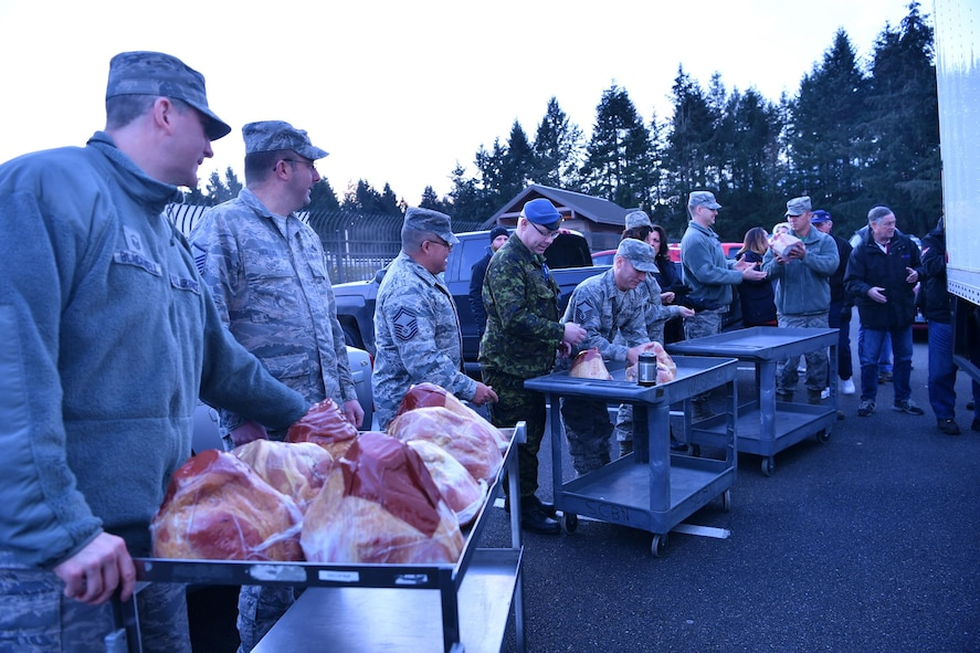 Col. Brett Bosselmann, 225th Air Defense Squadron commander, third from right, assists with the delivery of holiday hams donated to the Western Air Defense Sector during Operation Ham Grenade Dec 16.  Members of the Association of the United States Army, the Air Force Association, local business leaders and the Pierce Military and Business Alliance, delivered 20 holiday hams to WADS junior servicemembers as a way to show their appreciation and support.  (U.S. Air National Guard photo by Kimberly D. Burke)