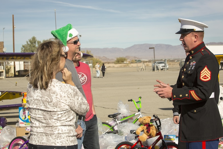Staff Sgt. Jason Slye, company master gunner, 4th Tank Battalion, thanks volunteers from the Redlands Airport Association who delivered toys to Twentynine Palms Airport as part of the 2nd annual Toys for Tots Fly-in, Dec. 10, 2016. (Official Marine Corps photo by Cpl. Levi Schultz/Released)