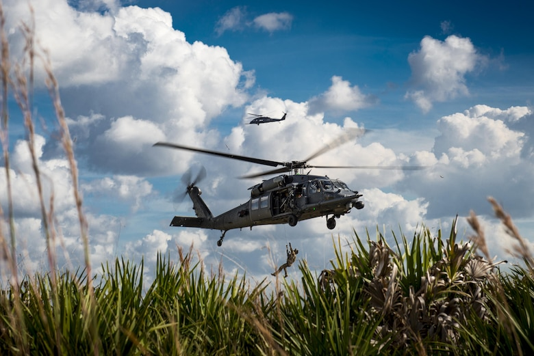 A pararescueman from the 38th Rescue Squadron rides a hoist back into a 41st RQS HH-60G Pave Hawk during a 'spin-up' exercise, Dec. 13, 2016, at Avon Park Air Force Range, Fla. During the spin-up, the 41st RQS, alongside mission partners from the 38th and 71st Rescue Squadrons, conducted high-tempo rescue operations designed to mimic the missions they will fly downrange. They based their operations out of Patrick AFB and flew missions to Avon Park Air Force Range, Fla.(U.S. Air Force photo by Staff Sgt. Ryan Callaghan)