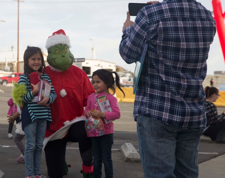 Sophia Trevino, 7, and Selene Trevino, 4, daughters of Staff Sgt. Tim Trevino, communication maintenance chief, Marine Corps Logistics Operations Group, get to meet the Grinch during Marine Corps Community Service's annual Combat Center Toy Giveaway at the West Gym aboard Marine Corps Air Ground Combat Center, Twentynine Palms, Calif., Dec. 10, 2016. (Official Marine Corps photo by Cpl. Medina Ayala-Lo/Released)