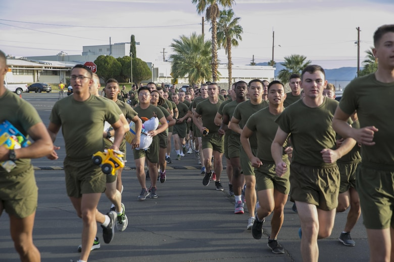 Students and staff of Marine Corps Communication-Electronics School carry toys to donation bins during the Toys for Tots Fun Run aboard Marine Corps Air Ground Combat Center, Twentynine Palms, Calif., Dec. 14, 2016. (Official Marine Corps photo by Lance Cpl. Dave Flores/Released)