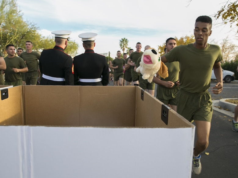 A student from the Marine Corps Communication-Electronics School drops off a toy in a donation bin during the Toys for Tots Fun Run aboard Marine Corps Air Ground Combat Center, Twentynine Palms, Calif., Dec. 14, 2016. (Official Marine Corps photo by Lance Cpl. Dave Flores/Released)