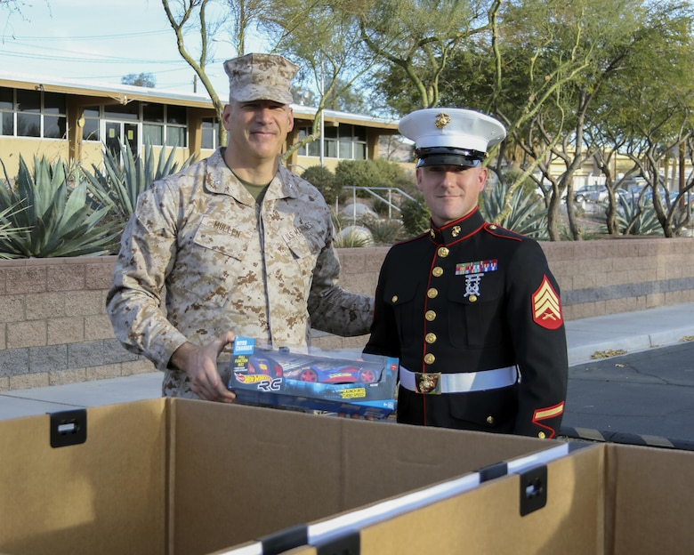 Brig. Gen. William F. Mullen III, Combat Center Commanding General, gives Sgt. Joshua Ulrich, radar maintenance chief, Marine Corps Communication-Electronics School, the first gift for donation during the Toys for Tots Fun Run aboard Marine Corps Air Ground Combat Center, Twentynine Palms, Calif., Dec. 14, 2016. (Courtesy photo by Kathleen Arbaczewski/Released)