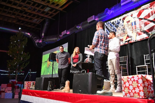 Staff Sgt. Daniel Cuevas, 309th Missile Maintenance Group, and his wife Patricia are granted their holiday wish by George Hill and Jeff Wells during the G3 Holiday Bash, Park City, Utah, Dec. 15, 2016. Four Hill Air Force Base families were granted wishes during the event. (U.S. Air Force photo/R. Nial Bradshaw)