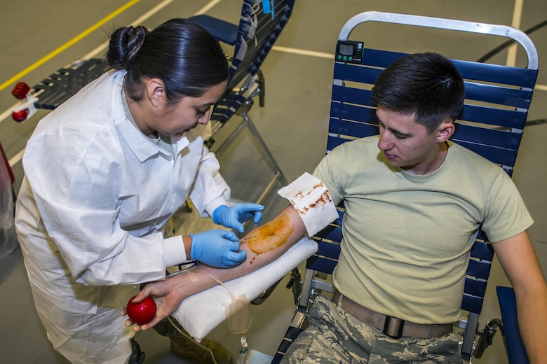 U.S. Army Specialist Dianna McDaniel, medical lab technician, inserts an intravenous line into the arm of Airman 1st Class Shawn Green, 27th Special Operations Civil Engineer Squadron power production technician, during an Armed Forces Blood Program blood drive in bldg. 54's gym on Nov. 16, 2016, Cannon AFB, N.M. U.S. Army medical personnel traveled from Ft. Bliss, Texas, to a with the blood drive. (U.S. Air Force photo by Senior Airman Luke Kitterman/Released)