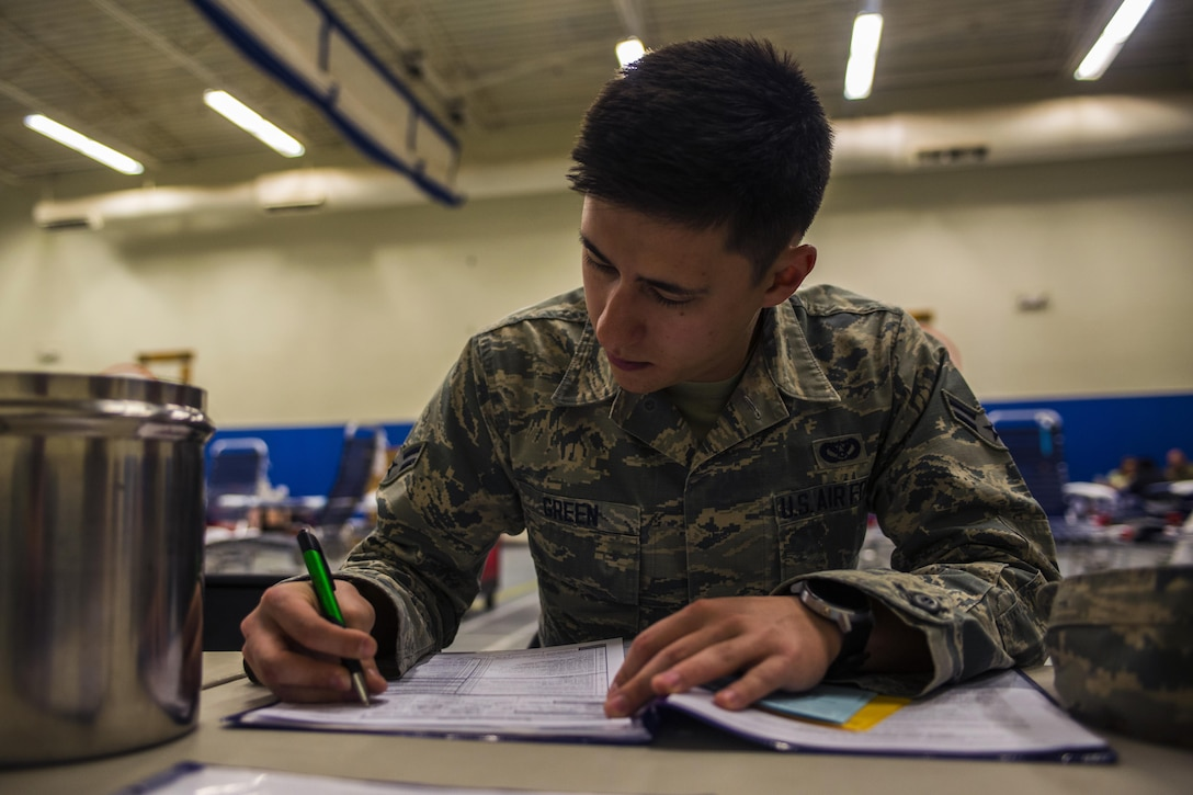 Airman 1st Class Shawn Green, 27th Special Operations Civil Engineer Squadron power production technician, fills out paperwork before donating blood at an Armed Forces Blood Program blood drive in bldg. 54's gym on Nov. 16, 2016, Cannon AFB, N.M. The ASBP was established more than 60 years ago as a joint field operating agency. (U.S. Air Force photo by Senior Airman Luke Kitterman/Released)