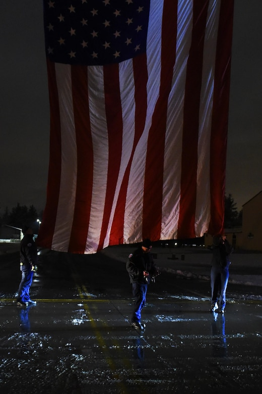 "Members of the Joint Base Lewis-McChord fire department as well as the South King County fire departments raise a flag over the road way on the McChord Filed, Wash. Dec., 9, 2016. A funeral procession staging at JBLM would pass underneath the flag on their way to the Tacoma Dome in Tacoma, Wash., for the funeral of Tacoma Police Officer Reginald ""Jake"" Gutierrez. (U.S. Air Force photo/Tech. Sgt. Tim Chacon)"