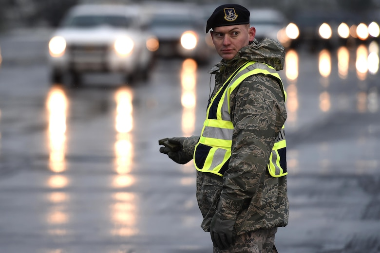 "Senior Airman Jordan Proctor, 627th Security Forces Squadron, directs law enforcement vehicles on Joint Base Lewis-McChord, Wash., Dec. 9, 2016. More than 450 law enforcement vehicles from all across the country staged at JBLM for the funeral of Tacoma Police Officer Reginald ""Jake"" Gutierrez. (U.S. Air Force photo/Tech. Sgt. Tim Chacon)"