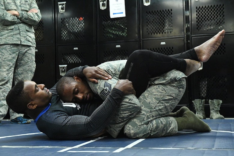 Lorenz Larkin, a professional mixed martial artist competing in the Welterweight division of the Ultimate Fighting Championship, demonstrates a grappling technique to Tech. Sgt. Franklin Mosley, 633rd Security Forces flight chief and trainer, during a combatives course at Joint Base Langley-Eustis, Va., Dec. 8, 2016. In addition to the fact that combatives are part of Mosley's job in the Air Force, he also does mixed martial arts training to help him sharpen his mental, physical, social and spiritual fitness. (U.S. Air Force photo by Staff Sgt. Nick Wilson)