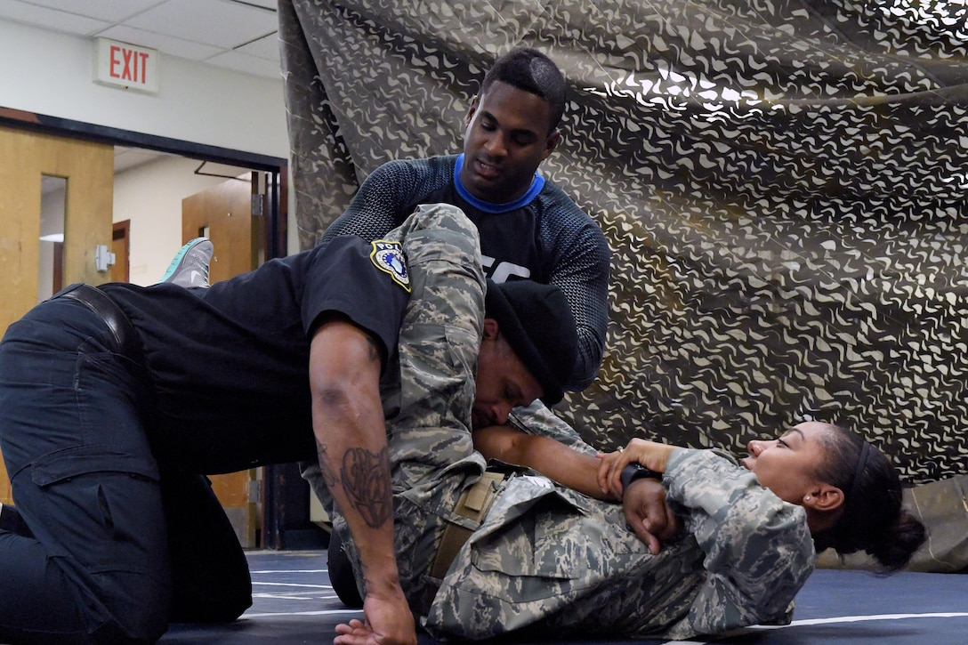 Senior Airman Jexsira Watts, 633rd Security Forces Squadron response force leader, applies a triangle choke on Tony Molette, 633rd SFS law enforcement officer, with assistance from Lorenz Larkin, a professional Ultimate Fighting Championship mixed martial artist, during a combatives course at Joint Base Langley-Eustis, Va., Dec. 8, 2016. Larkin's appearance was part of a distinguished visitor tour where military members and dependents had an opportunity to meet and get autographs from Shevchenko, other UFC fighters and radio hosts throughout the week. During the tour the UFC athletes spoke with service members about similarities between the UFC and the U.S. Armed Forces. (U.S. Air Force photo by Staff Sgt. Nick Wilson)