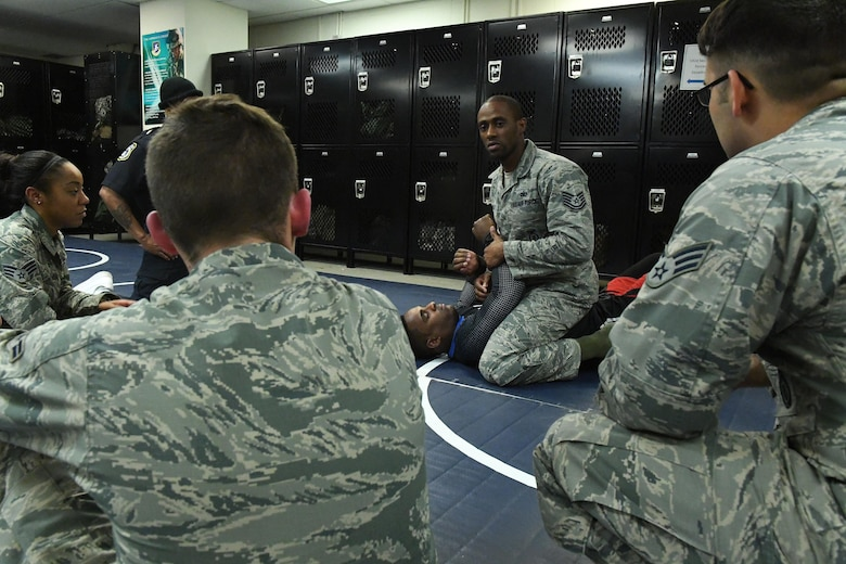 Tech. Sgt. Franklin Mosley, 633rd Security Forces flight chief and combatives course instructor, gives a demonstration with Lorenz Larkin, a professional Ultimate Fighting Championship mixed martial artist, on how to execute various grappling techniques from the full mount position during a combatives course at Joint Base Langley-Eustis, Va., Dec. 8, 2016. Larkin spoke to service members about how the mental toughness that is required to become successful and reach goals, whether in the UFC or military. He also toured both of JBLE's installations alongside a group of mixed-martial arts athletes, journalists and celebrities throughout the week as part of a military appreciation visit. (U.S. Air Force photo by Staff Sgt. Nick Wilson)