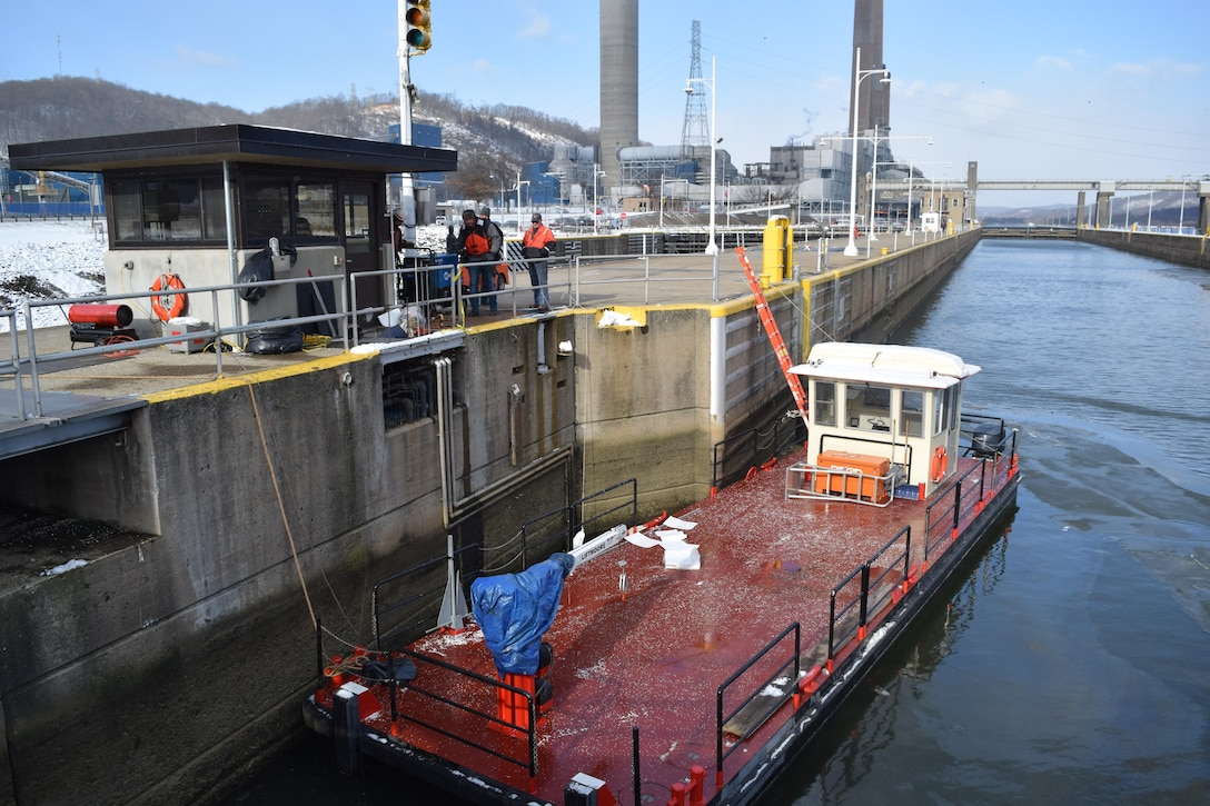 A workboat rests on the main chamber lock wall as repair crews above work to fix New Cumberland Locks and Dam's hydraulic system.