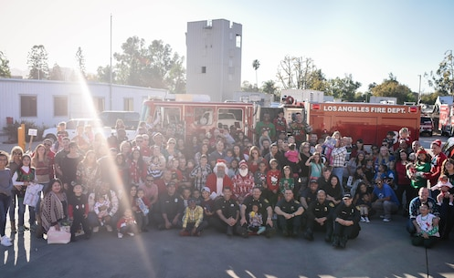 Marines and their families from Recruiting Station Los Angeles gather for a photo with firefighters during Recruiting Station Los Angeles' Christmas party at the Los Angeles Fire Department Station 88 in Sherman Oaks, Calif., Dec. 3, 2016. Marines and their families gathered, sporting their ugly sweaters and enjoying holiday festivities as a unit. (Photo by Arlene Ward/Released)