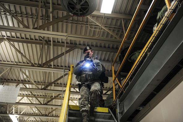 U.S. Air Force Airman 1st Class Trevor Holman, a 354th Security Forces Squadron response force leader, scans the area as he walks down the stairs Dec. 14, 2016, at the 168th Logistics Readiness Squadron building on Eielson Air Force Base, Alaska. Holman was participated in an active shooter drill hosted by the 168th Wing and 354th Fighter Wing during Arctic Gold 17-2. (U.S. Air Force photo by Airman Isaac Johnson)