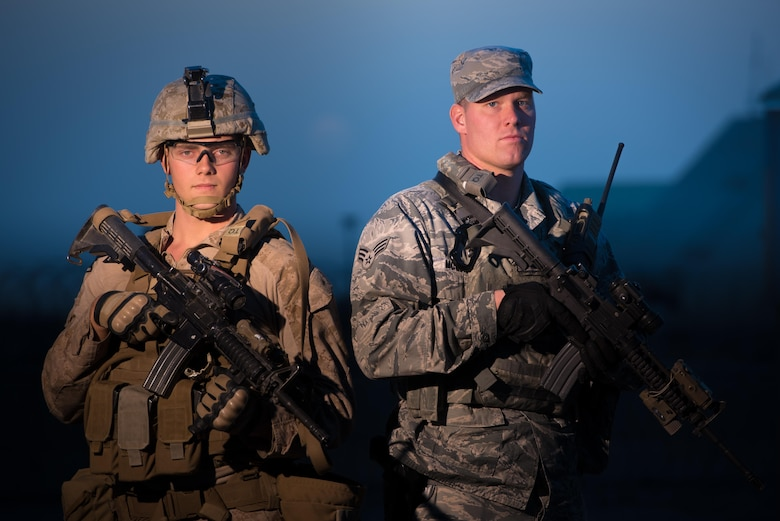 U.S. Air Force Senior Airman Shaun McQuiston and U.S. Marine Corps Lance Cpl. Michael Hall, both 407th Expeditionary Security Forces Squadron, pose for a photo at the 407th Air Expeditionary Group, Southwest Asia Dec. 17, 2016. The expeditionary security forces unit uses active duty and reserve Airmen and Marines as well as Polish forces working together to keep the base secure.  (U.S. Air Force photo/Master Sgt. Benjamin Wilson)(Released)