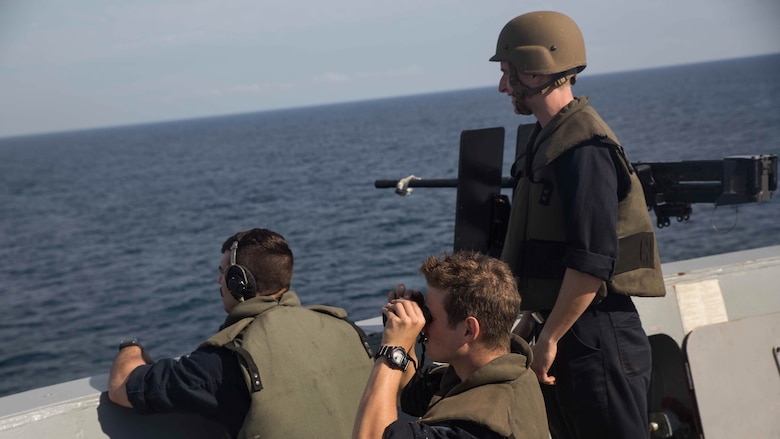 Sailors with the small caliber arms team observe and report any vessels they see from the forecastle aboard USS Mesa Verde (LPD 19), during a simulated straight transit to rehearse a defense of the amphibious task force mission during Amphibious Ready Group Marine Expeditionary Unit Exercise Dec. 13, 2016. During the three-week training evolution, Marines will tackle a wide range of operations and scenarios enhancing interoperability and amphibious warfare capabilities with their Navy counterparts. The additional firepower Marines provide improves the Navy-Marine Corps team's ability to defend the naval vessels of the Bataan Amphibious Ready Group.