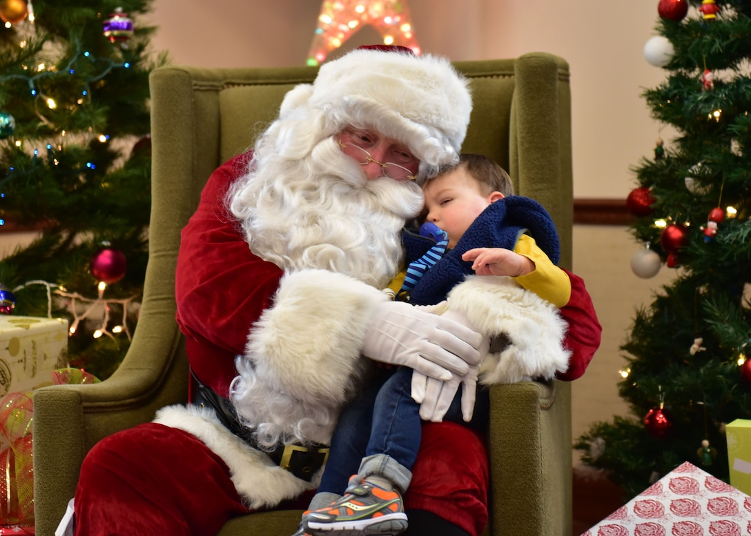 A child rests with Santa after waiting in line at the Niagara Falls Air Reserve Station on December 17, 2016. Santa made his annual visit aboard a Niagara C-130 Hercules for the last time as the 914th Airlift Wing is transitioning to the KC-135 Stratotanker. (U.S. Air Force photo by Staff Sgt. Richard Mekkri)
