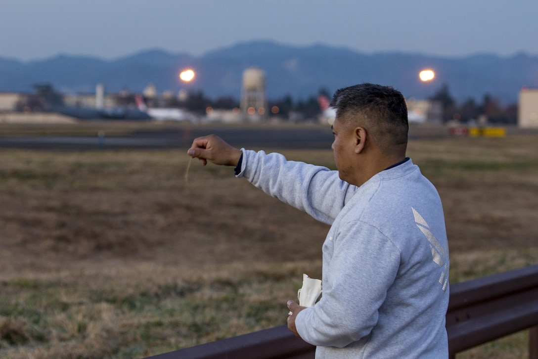 Master Sgt. Edward M. Silversmith, 374th Maintenance Squadron flight chief, performs a traditional Navajo morning ritual and prayer while sprinkling an offering of corn pollen on Dec. 9, 2016, at Yokota Air Base, Japan. In Navajo culture, it is customary to get up before the sun rise and do the ritual followed by a run east towards the rising sun. (U.S. Air Force photo by Airman 1st Class Donald Hudson)