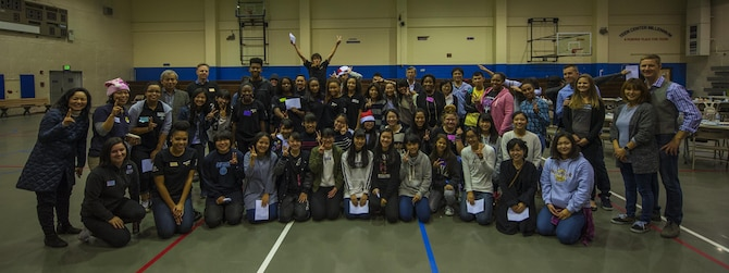 Okinawan and American schoolchildren, along with volunteers from the two communities, take part in a community event meant to build new relationships for the students and to provide insight into another culture, Dec. 17, 2016, at the teen center on Kadena Air Base, Japan. The event included food, games, holiday lights and a song sung in both Japanese and English. (U.S. Air Force photo by Airman 1st Class Nick Emerick/Released)