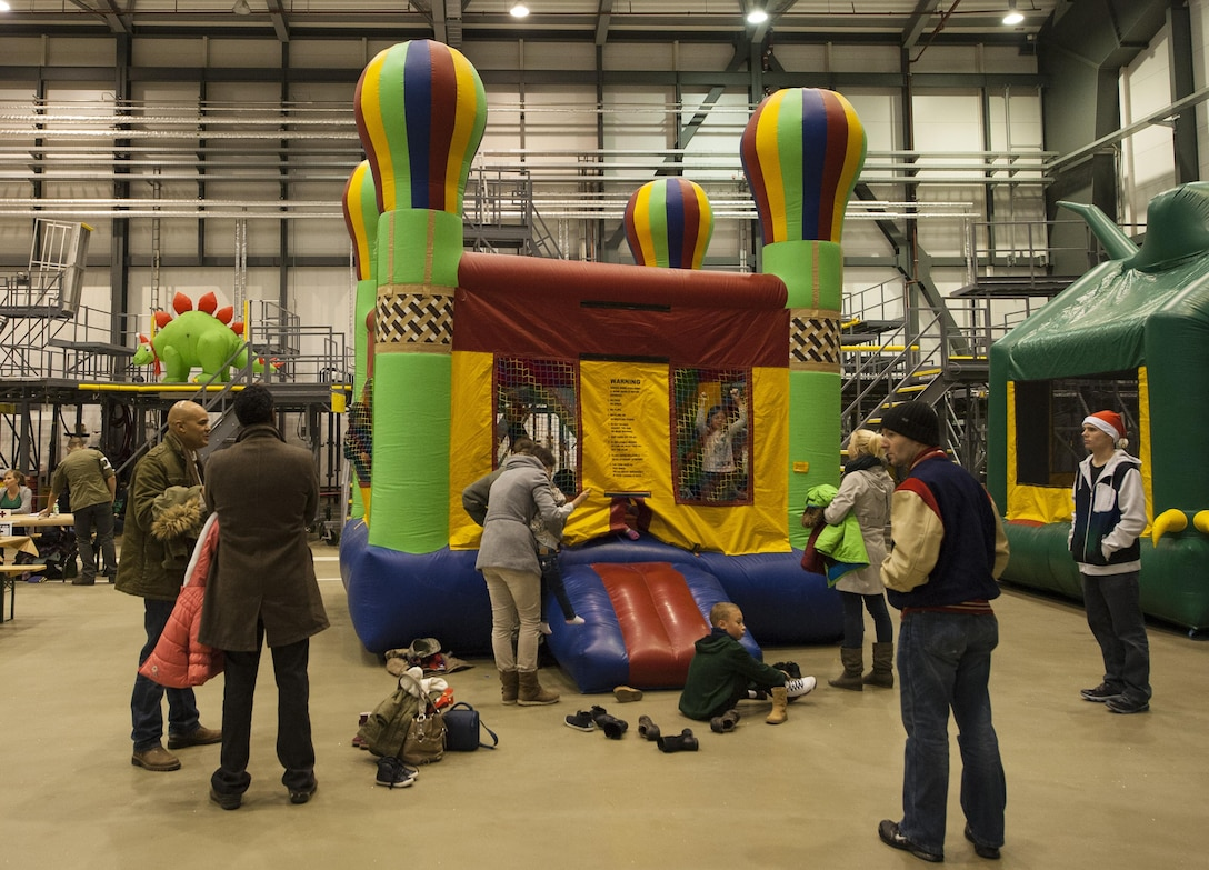 Kids play in a bounce house during a Christmas event held at Ramstein Air Base, Germany, Dec. 16, 2016. Children played in jumping castles and everyone participated in penguin bowling, face painting, a photo booth and watched movies. (U.S. Air Force photo by Airman 1st Class Lane T. Plummer)