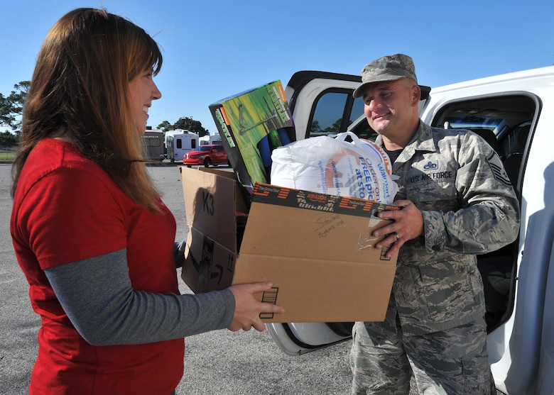 Aimee Bright, Tyndall Spouses Club president, helps Master Sgt. Kevin Marshall, 43d Aircraft Maintenance Unit specialist section chief, load donated gifts into a vehicle for delivery during Operation Angel Tree at the base Thrift Shop on Tyndall Air Force Base, Fla., Dec. 16, 2016. The event mainly focuses to help single income and larger families during the holiday season. (U.S. Air Force photo by Senior Airman Ty-Rico Lea/Released)