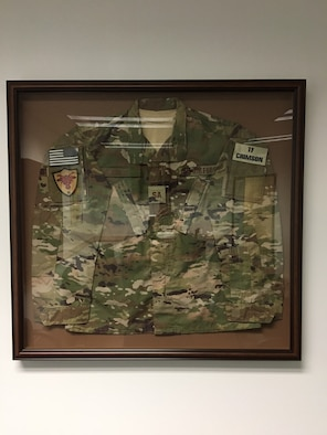 Inside the newly dedicated Special Agent Michael A. Cinco Facility at Beale Air Force Base, Calif., is a shadow box with SA Cinco's utility uniform he wore as a member of Team Crimson in Afghanistan. (U.S. Air Force photo/Airman Tristan D. Viglianco 9 RW/PA)