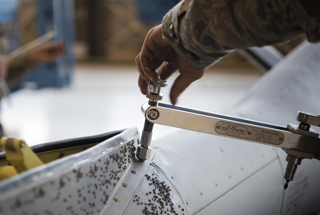 Tech. Sgt. Alfonso Vigil 92nd Maintenance Squadron hydraulics NCO in charge of dayshift, removes a stripped screw from the saddle panel located on the refueling boom Dec. 16, 2016, at Fairchild Air Force Base, Wash. The boom operator uses the ruddervators to guide the boom to another jet during air refueling operations. (U.S. Air Force photo/ Airman 1st Class Sean Campbell)