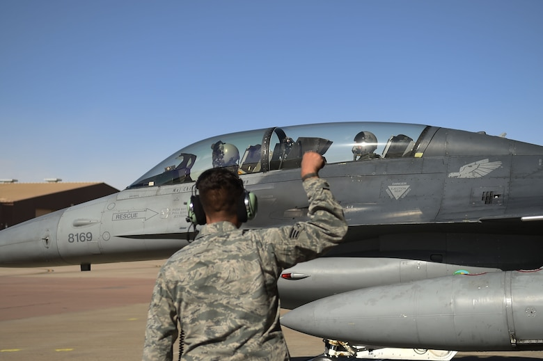 Senior Airman Joseph Garcia, 54th Aircraft Maintenance Squadron crew chief, gives the go sign for Maj. Matthew Marshall, 54th Fighter Group fighter pilot, and U.S. Rep. Steve Pearce, New Mexico 2nd district, for their flight, Dec. 16, 2016, Holloman Air Force Base, N.M. Pearce was offered an orientation flight on the F-16 Fighting Falcon, to better understand the capabilities and mission of the F-16. (U.S. Air Force photo by Tech. Sgt. Amanda N. Junk)