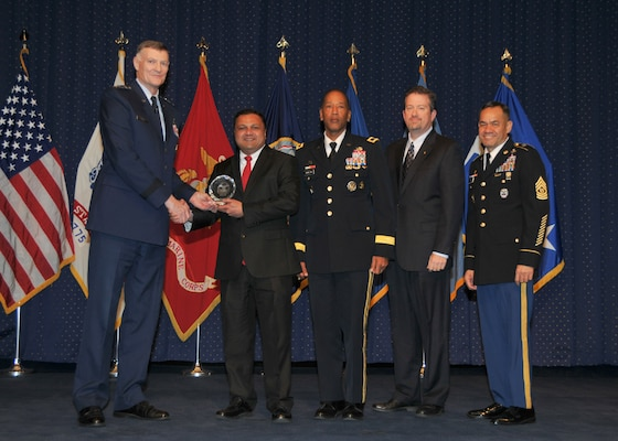 DLA Director Air Force Lt. Gen. Andrew Busch presents Kaushal Desai, Subsistence, with a DLA Leader of the Year award at the 49th Annual DLA Employee Recognition Award Ceremony Dec. 15 at DLA Headquarters.
