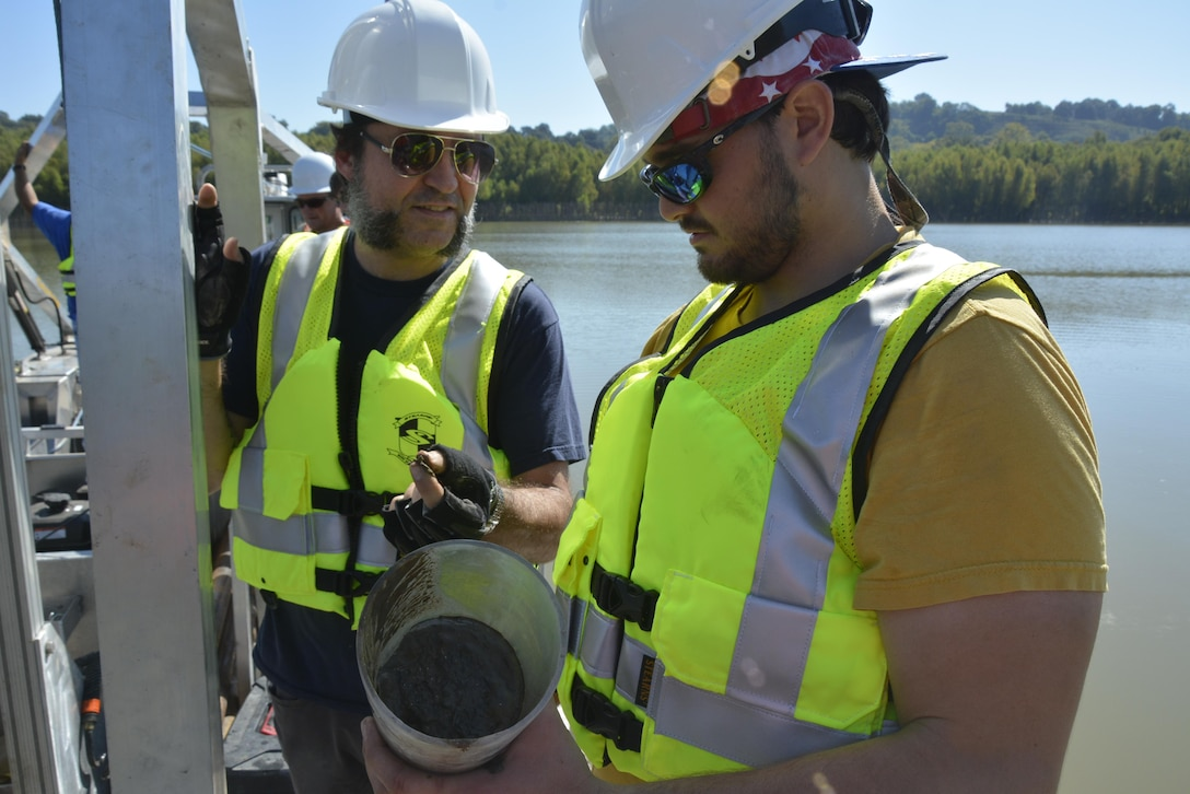 Researchers Anthony Priestas and Brandon Boyd from ERDC's Coastal and Hydraulics Laboratory examine a core sample collected from the lab's new coring barge on the Mississippi River near Vicksburg.