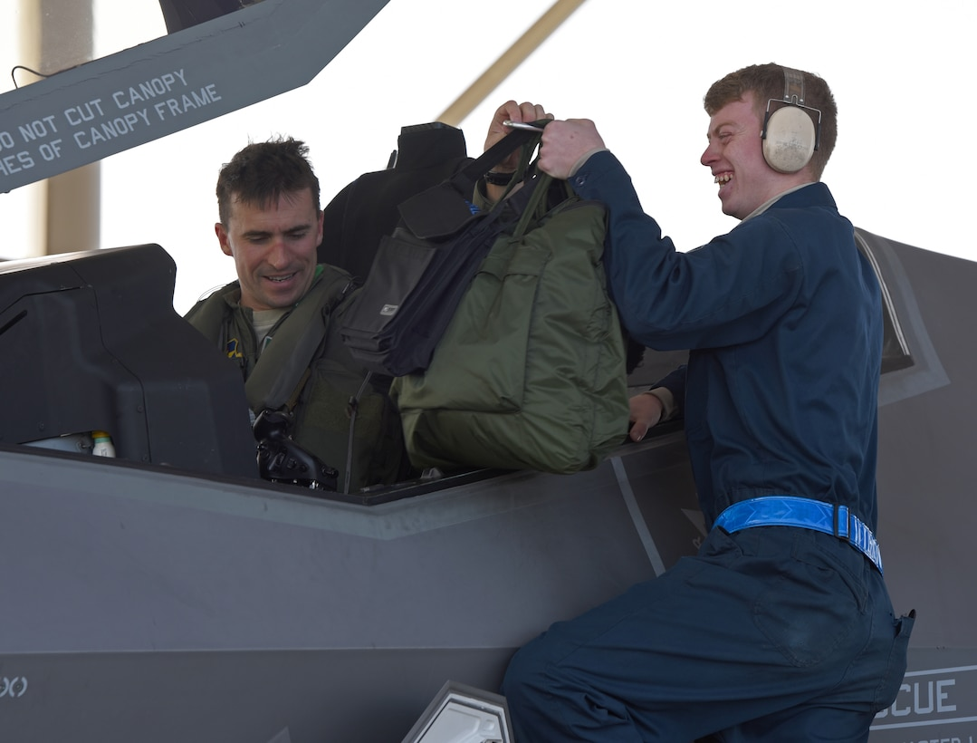 U.S. Air Force Senior Airman Christopher Trimarco, 33d Aircraft Maintenance Squadron F-35A crew chief, retrieves gear from Maj. Bradley Zimmerman, 33d Operation Support Squadron assistant wing weapons officer, after landing during Checkered Flag 17-01, Dec. 8, 2016, at Tyndall Air Force Base, Florida. Checkered Flag facilitates integration between fifth and fourth-generation aircraft communities. These exercises are critical to hone the tactics techniques and procedures (TTP's) for the aircraft's inevitable deployment fighting alongside other combat assets. While the exercise is prime opportunity to learn about how we fly the aircraft, it presents the same learning opportunities for preventative and restorative maintenance. (U.S. Air Force photo by Staff Sgt. Peter Thompson)