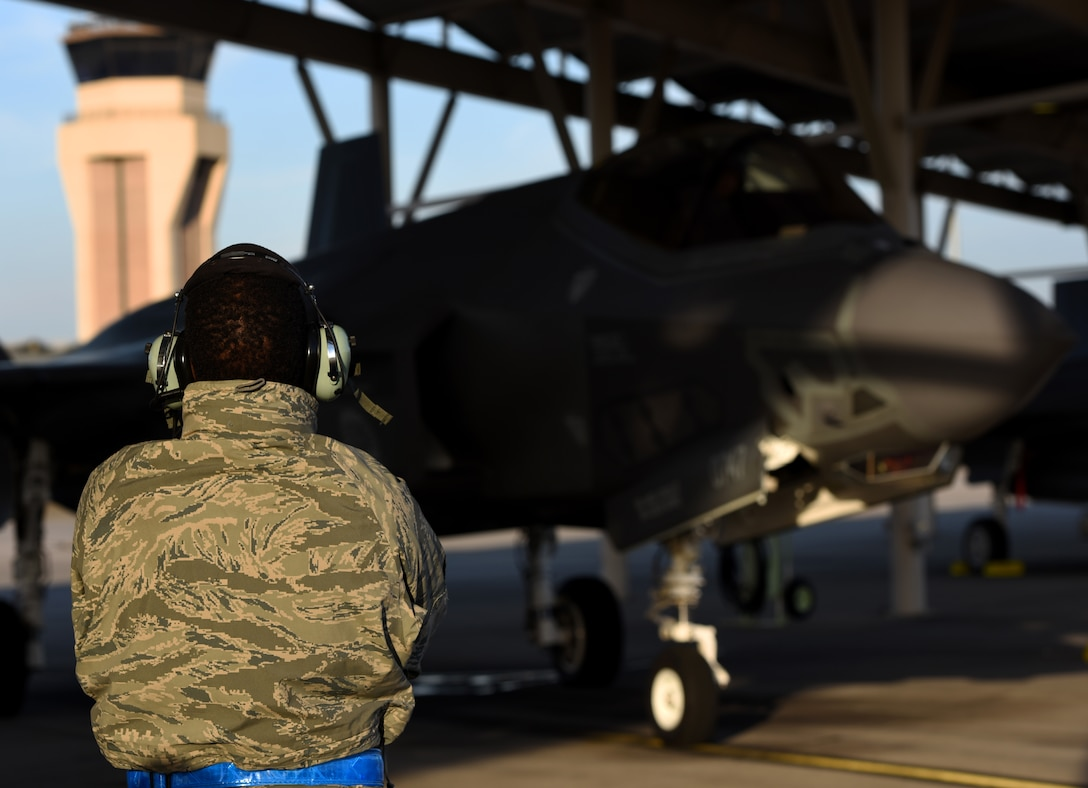 U.S. Air Force Senior Airman Lonnie Prater, 33d Aircraft Maintenance Squadron F-35A assistant dedicated crew chief, stands near and F-35A Lightning II during Checkered Flag 17-01, Dec. 8, 2016, at Tyndall Air Force Base, Florida. Checkered Flag facilitates integration between fifth and fourth-generation aircraft communities. These exercises are critical to hone the tactics techniques and procedures (TTP's) for the aircraft's inevitable deployment fighting alongside other combat assets. While the exercise is prime opportunity to learn about how we fly the aircraft, it presents the same learning opportunities for preventative and restorative maintenance. (U.S. Air Force photo by Staff Sgt. Peter Thompson)