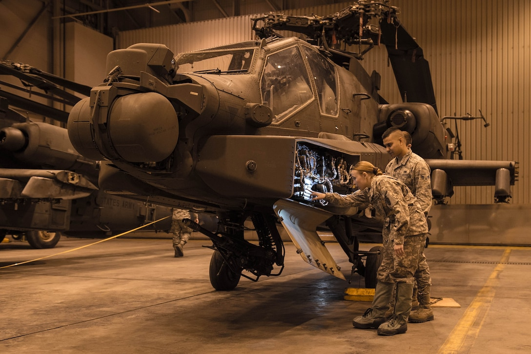 An Airman from the 821st Contingency Response Squadron, and a Soldier from the 1st Attack Reconnaissance Battalion, 25th Combat Aviation Brigade, performs a joint inspection on an AH-64 Apache helicopter before being loaded onto a C-17 Globemaster III, Dec. 11, 2016, at Eielson Air Force Base, Alaska. A contingency response team was sent to Eielson AFB to support the Army's Rapid Alaska Airlift Week exercise. (U.S. Air Force photo by Staff Sgt. Robert Hicks)