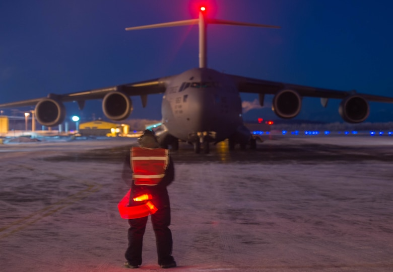 Staff Sgt. Justin Fraissinet, 821st Contingency Response Squadron maintainer, prepares to marshal a C-17 Globemaster III aircraft, Dec. 12, 2016, at Eielson Air Force Base, Alaska. A contingency response team was sent to Eielson AFB to support the Army's Rapid Alaska Airlift Week exercise. (U.S. Air Force photo by Staff Sgt. Robert Hicks)