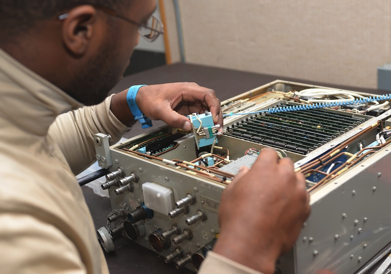 Airman 1st Class Terre Camille, an avionics technician assigned to the 28th Maintenance Squadron, installs an amp into a Line Replaceable Unit at Ellsworth Air Force Base, S.D., Dec. 6, 2016. An LRU is a modular component of complex electronic systems for aircraft that can be replaced quickly, and generally with a minimum of tools. (U.S. Air Force photo by Airman 1st Class Donald C. Knechtel)