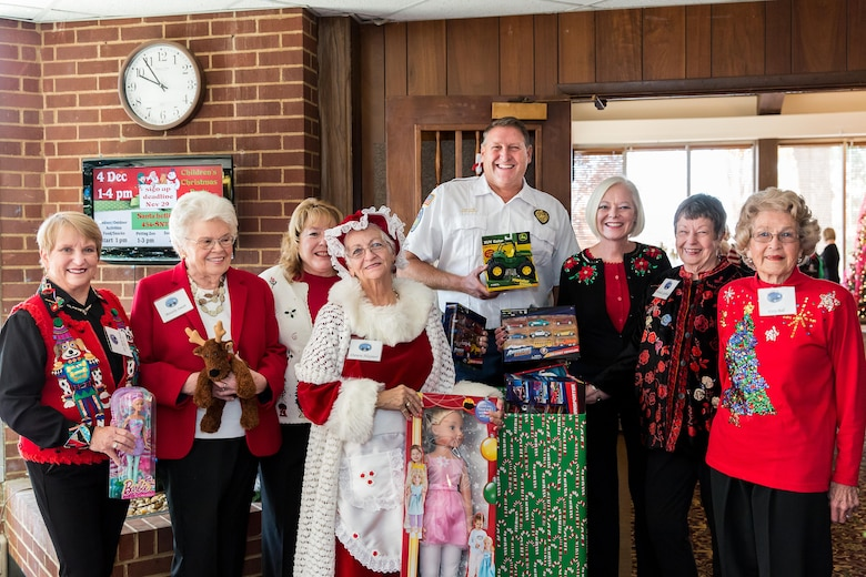 Capt. Jeff Smith (fifth from the left), with the Tullahoma Fire Department, collects gifts provided by the AEDC Woman's Club for the Toys for Tots program. Also pictured is Anne-Marie Pender, Beverly Smith, Vicky Porter, Dawn Hayner, Suzette McCrorey, Wanda Gobbell and Kitty Ball. (Courtesy photo)