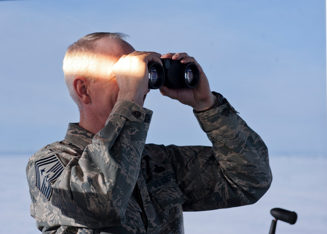 Chief Master Sgt. Alan Boling, 8th Air Force command chief, looks through binoculars at Minot Air Force Base, N.D., Dec. 15, 2016. Boling toured Minot's facilities, including the air traffic control tower and spoke with 5th Bomb Wing Airmen. (U.S. Air Force photo/Airman 1st Class J.T. Armstrong)